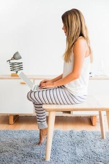 Dame, die zu hause mit laptop auf beinen sitzt