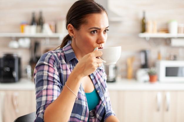 Dame entspannt und trinkt heißen grünen tee aus porzellantasse während des frühstücks in hübsche dame, die morgens während der frühstückszeit in der küche sitzt und sich mit leckerem natürlichem kräutertee entspannt