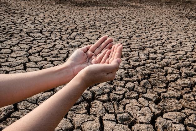 Dame hand, die auf regenwasser, rissige und trockene erde in trockener landschaftslandschaft wartet