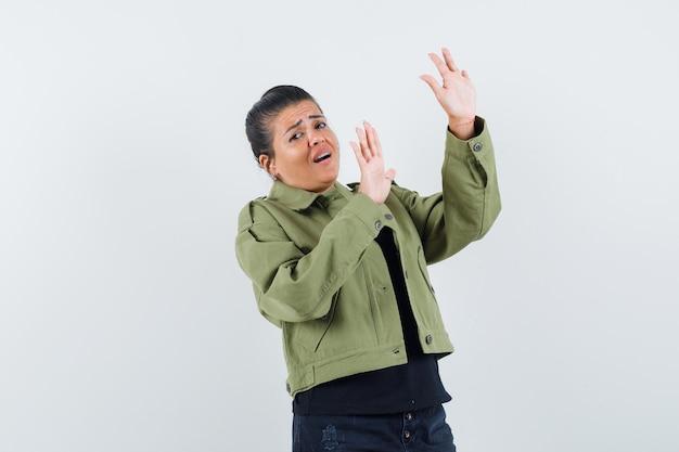 Dame hebt die hände, um sich in der jacke zu verteidigen