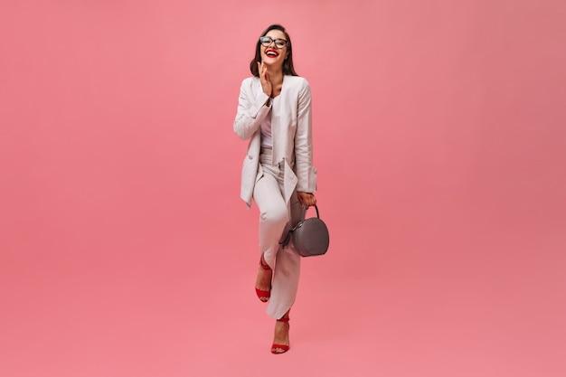 Dame im anzug lacht und hält tasche auf rosa hintergrund. schöne geschäftsfrau in den gläsern und mit dem roten lippenstift, der auf kamera aufwirft.