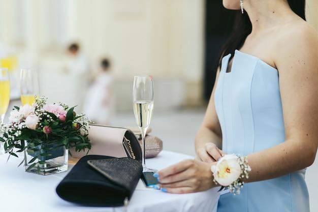 Dame im blauen kleid mit blume über ihrem wirst sitzt am tisch