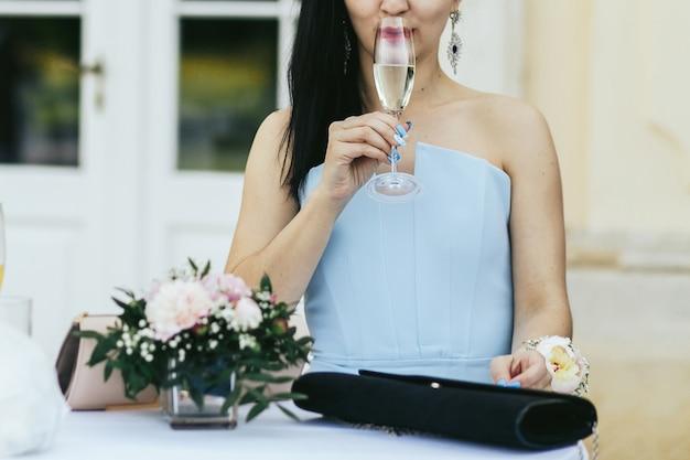 Dame im blauen kleid trinkt kalten champagner