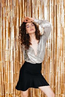 Dame im festlichen outfit, das auf goldenem hintergrund artig posiert