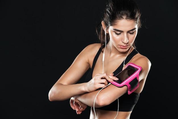 Dame im fitnessstudio, die über der schwarzen wand steht und beiseite schaut, während sie musik mit kopfhörern hört