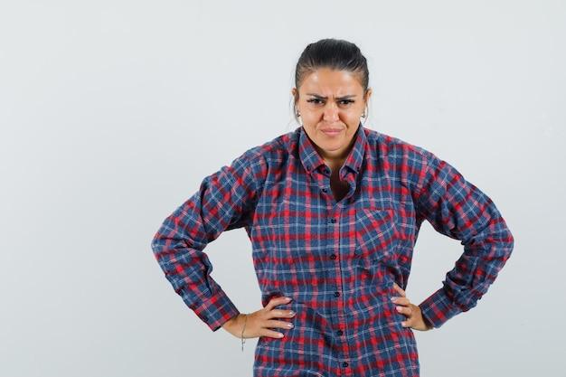 Dame im freizeithemd, die hände auf taille hält und boshaft schaut, vorderansicht.