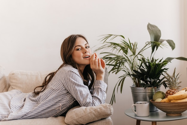Dame im gestreiften pyjama, der im wohnzimmer ruht. frau liegt auf der couch neben obstteller