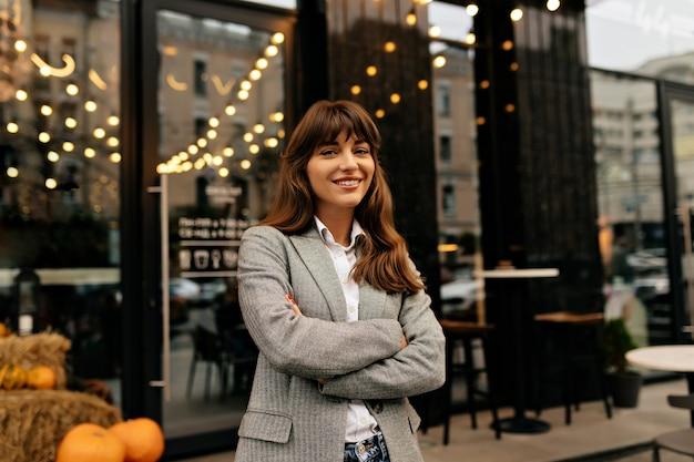 Dame im grauen anzug, der kamera auf hintergrund des stilvollen cafés mit lichtern lächelt.