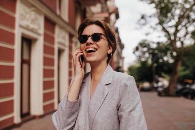 Dame im grauen anzug, die draußen lächelt und am telefon spricht. glückliche aufgeregte kurzhaarige frau in übergroßer jacke, die lacht und durch stadt geht