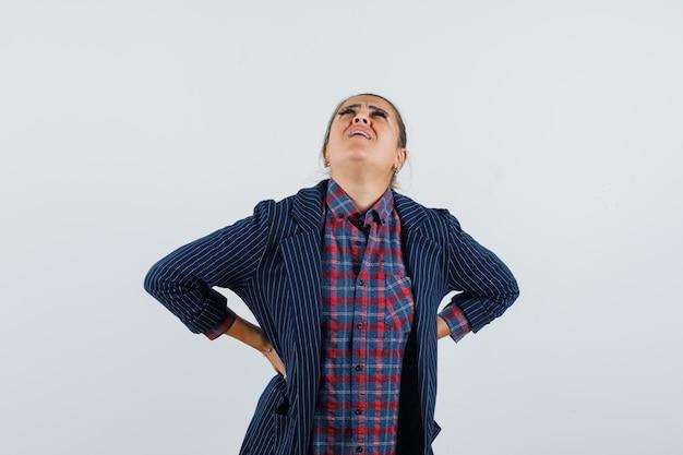 Dame im hemd, jacke, die unter rückenschmerzen leidet und unwohl aussieht, vorderansicht.