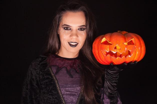 Dame im hexenkostüm, das einen kürbis über schwarzem hintergrund für halloween hält.
