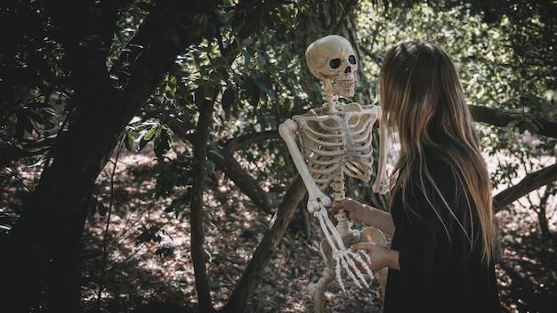 Dame im hexenkostüm, der skelett hält