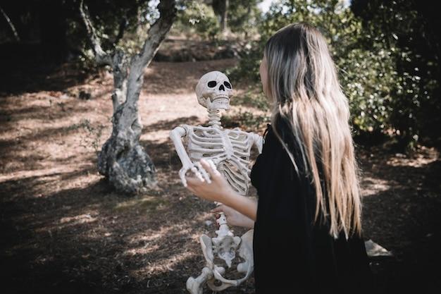 Dame im hexenkostüm, der skelett lehnt