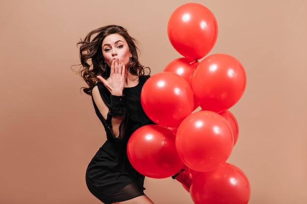 Dame im kurzen schwarzen kleid wirft auf beigem hintergrund mit luftballons auf und bläst kuss.