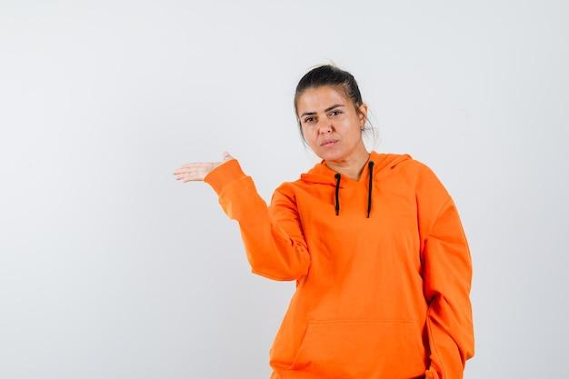 Dame im orangefarbenen hoodie zeigt eine einladende geste und sieht vernünftig aus looking