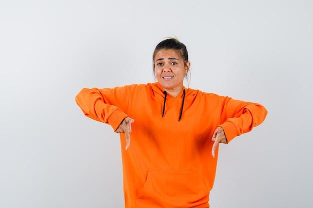 Dame im orangefarbenen hoodie zeigt nach unten und sieht selbstbewusst aus