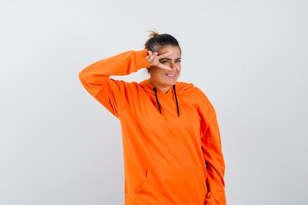 Dame im orangefarbenen hoodie zeigt v-zeichen auf dem auge und sieht glücklich aus
