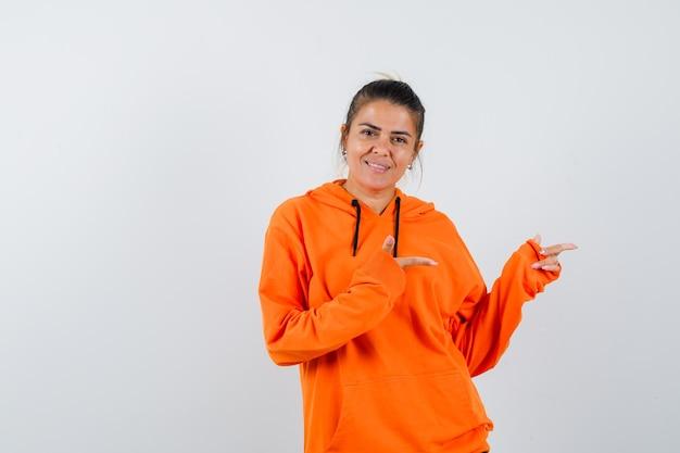 Dame im orangefarbenen hoodie zeigt zur seite und sieht fröhlich aus