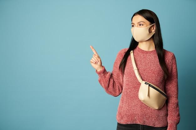 Dame im pullover und mit tasche posiert im studio