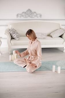 Dame im pyjama praktiziert yoga und sitzt in besonderer pose auf dem teppich zu hause