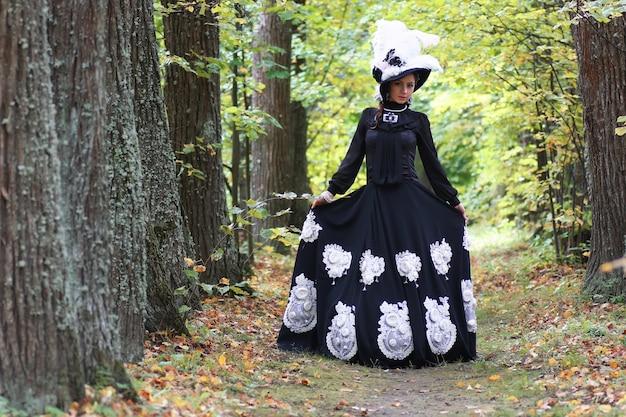 Dame im retro-kleid, die in der baumallee spaziert