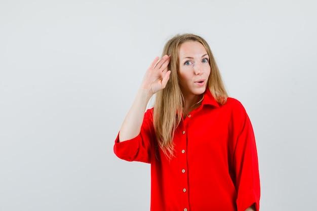 Dame im roten hemd, das grußgeste zeigt und selbstbewusst aussieht,