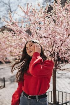 Dame im roten pullover lacht und spielt mit haaren vor dem hintergrund von sakuras. glückliche frau in der kaschmir-strickjacke und in den jeans, die draußen aufwerfen