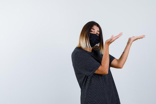 Dame im schwarzen kleid, medizinische maske, die einladende geste zeigt und selbstbewusst aussieht, vorderansicht.