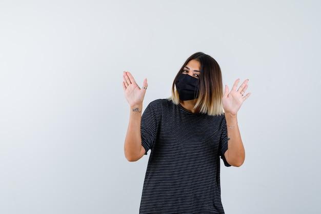 Dame im schwarzen kleid, medizinische maske, die stoppgeste zeigt und vorsichtig schaut, vorderansicht.