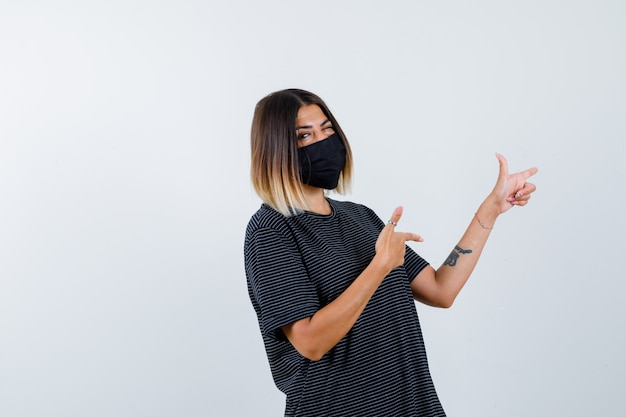 Dame im schwarzen kleid, medizinische maske zeigt nach rechts und sieht selbstbewusst aus, vorderansicht.