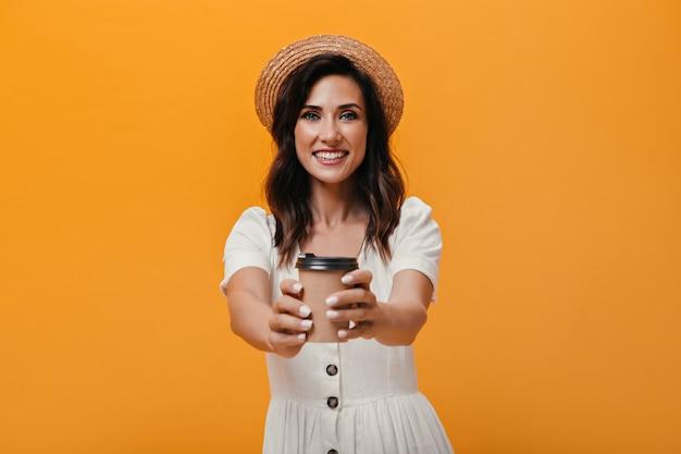Dame im stilvollen bootsfahrer und im weißen kleid, das glas kaffee auf orange hintergrund hält. dunkelhaarige frau im strohhut mit tee in den händen.