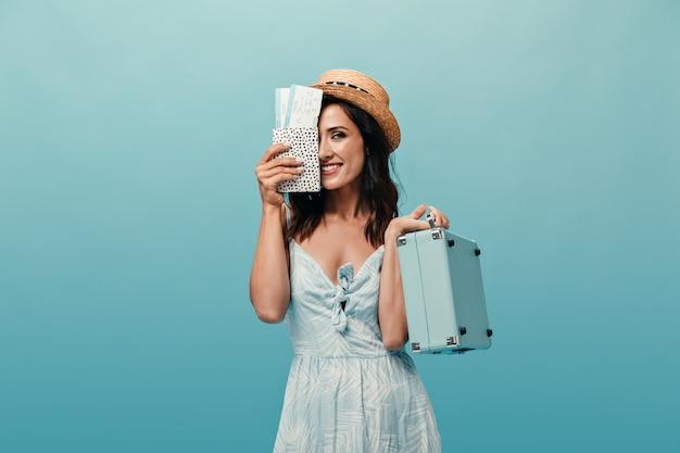Dame im strohhut bedeckt ihr gesicht mit eintrittskarten und hält koffer gegen blauen hintergrund. dunkelhaarige frau mit kurzen haaren und großen augen posiert.
