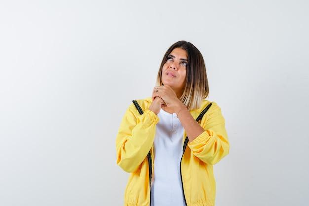 Dame im t-shirt, jacke, die hände in betender geste faltet und hoffnungsvoll aussieht, vorderansicht.