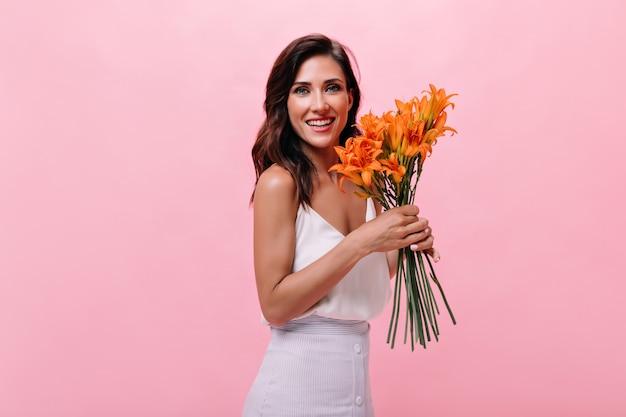 Dame im weißen outfit lächelt und hält blumenstrauß. schöne frau, die für kamera mit niedlichen orange blumen auf lokalisiertem hintergrund aufwirft.