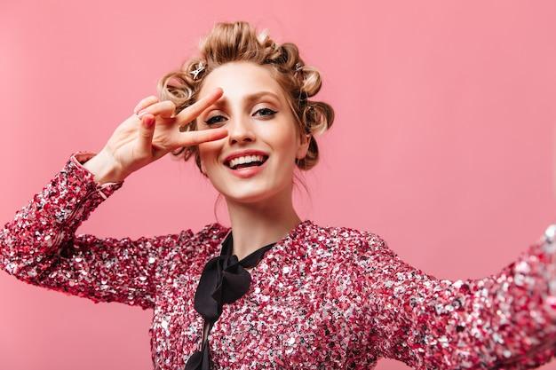 Dame in bluse mit pailletten nimmt selfie und zeigt friedenszeichen auf rosa wand