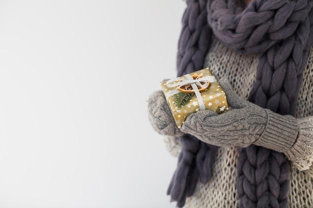 Dame in den handschuhen mit geschenkbox in den händen