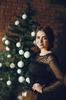 Dame in der nähe eines weihnachtsbaumes.
