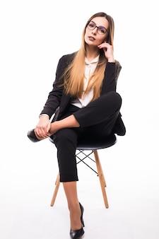 Dame in der schwarzen suite, die auf einem schwarzen stuhl auf weiß sitzt
