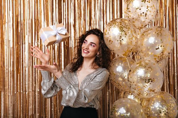 Dame in der silbernen bluse wirft geschenkbox auf goldenem hintergrund auf