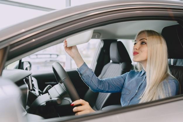 Dame in einem autosalon. frau, die das auto kauft. elegante frau in einem blauen kleid.