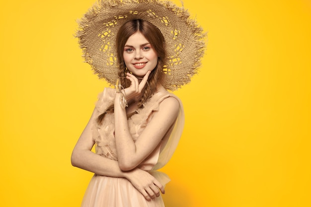 Dame in einem hut und kleid rotes haar gelber hintergrund modellporträt spaß. hochwertiges foto