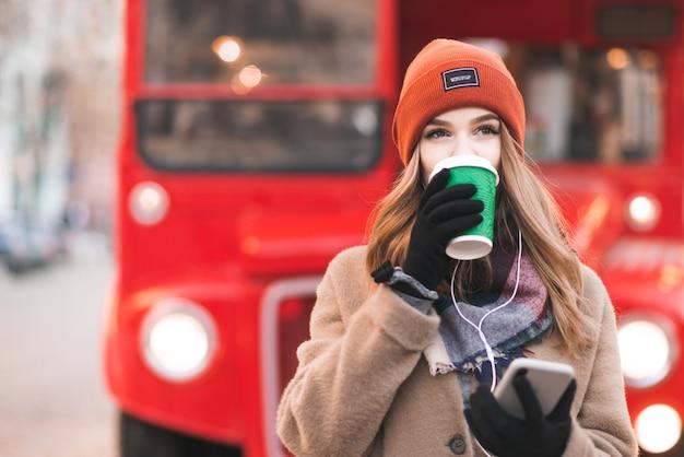 Dame in einem mantel und kopfhörern steht auf einem roten stadthintergrund mit einem smartphone in ihren händen, trinkt kaffee aus einer grünen tasse und schaut weg