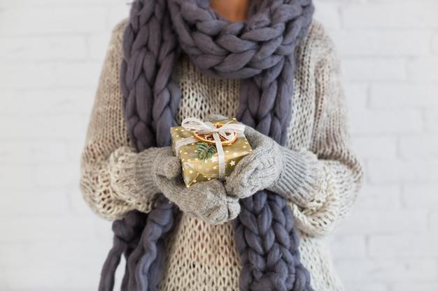 Dame in handschuhe und schal mit geschenkbox in der hand