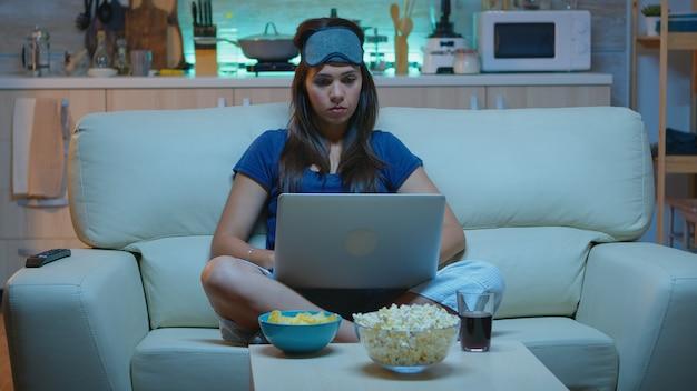 Dame in pyjamas und augenbedeckung auf der stirn, die auf dem laptop tippt und spät nachts fernsieht. freiberufler, der auf dem sofa sitzt und liest, schreibt, sucht, auf dem notebook mit internet-technologie surfen
