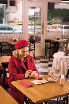 Dame in rot. elegante reife dame, die roten mantel trägt, der im café sitzt, kaffee trinkt und käsekuchen isst