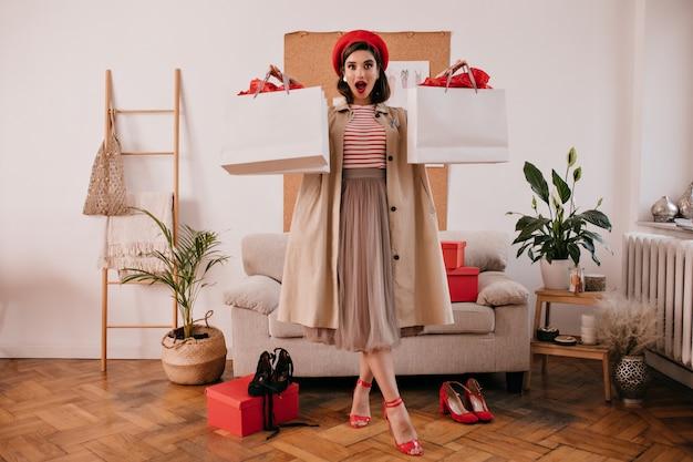 Dame in roter baskenmütze, beigem trenchcoat und kleid hält einkaufstaschen. erstaunte junge frau in langem rock und hellen absätzen schaut in die kamera.