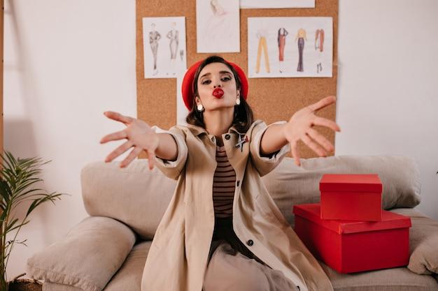 Dame in roter baskenmütze und beige outfit bläst kuss. nette junge frau mit roten lippen im langen modischen mantel, der an der kamera aufwirft.