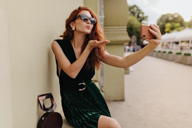 Dame in sonnenbrille bläst kuss beim selfie