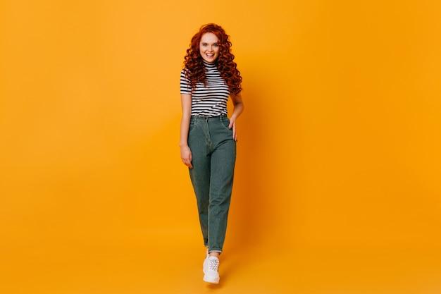 Dame in stilvoller jeanshose und gestreiftem oberteil, das auf orange raum aufwirft. in voller länge aufnahme von rothaarigen mädchen.