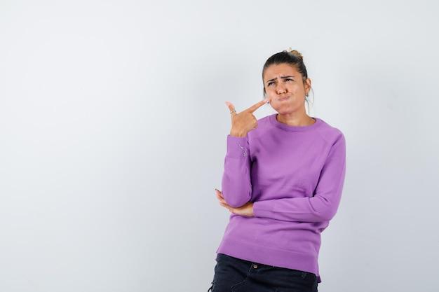 Dame in wollbluse zeigt auf ihre aufgeblasenen wangen und sieht düster aus looking